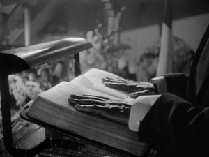 black and white photo of two hands resting on a book that is on a speaker's lectern